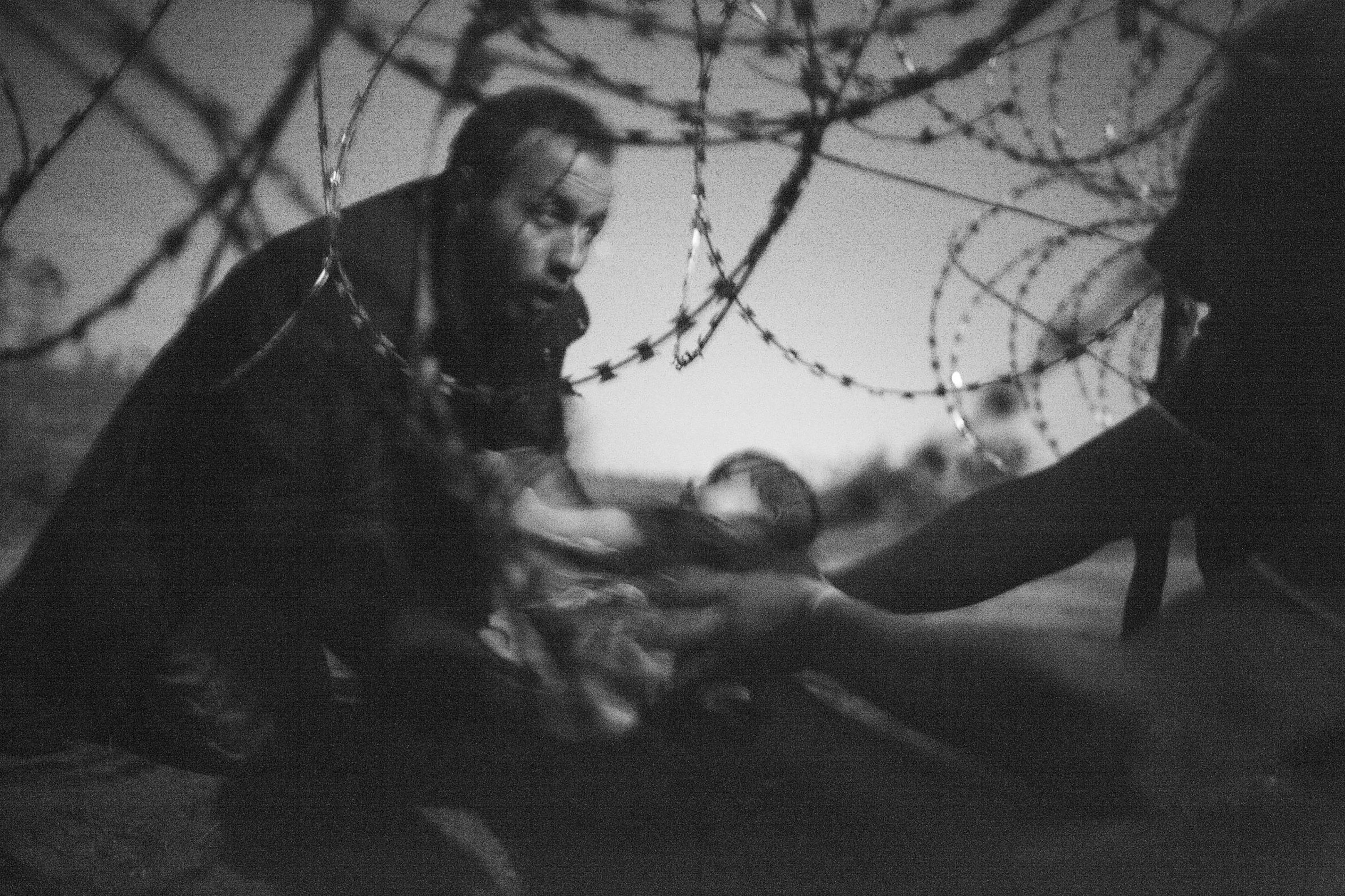 Warren Richardson, Australia, 2015, Hope for a New Life,  A man passes a baby through the fence at the Serbia/Hungary border in Röszke, Hungary, 28 August 2015.
